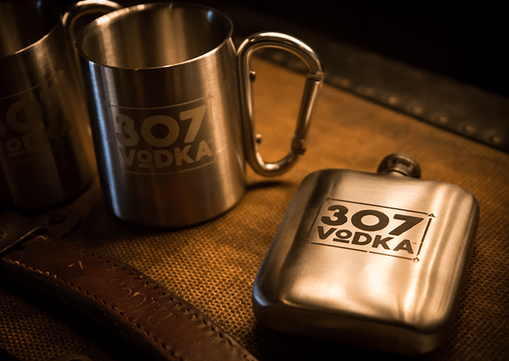 picture of metal cups and small flask with 307 vodka logo on them.